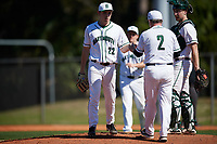 Dartmouth Big Green relief pitcher Michael Parsons (22) hands the ball to head coach Bob Whalen (2) as he makes a pitching change with catcher Kyle Holbrook (9) looking on during a game against the Villanova Wildcats on March 3, 2018 at North Charlotte Regional Park in Port Charlotte, Florida.  Dartmouth defeated Villanova 12-7.  (Mike Janes/Four Seam Images)