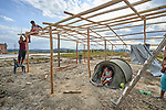 As his wife watches from a tent, Leonardo Cantillo and his son Fabian erect a shelter at Tarau-Paru, a Pemon indigenous village just inside Brazil. Cantillo and his family are refugees, having fled from Venezuela early in 2019 after new outbreaks of violence between the Venezuelan military and Pemon villagers.