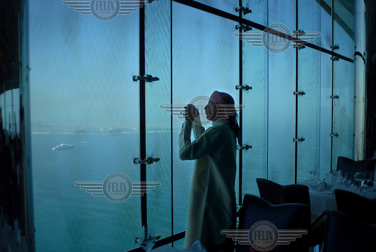 A man photographs the view from the restaurant at the top of Burj Al Arab Hotel.