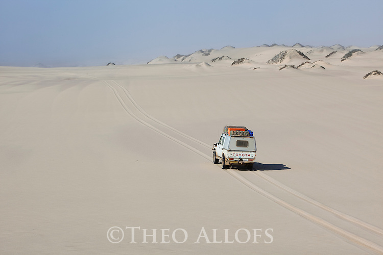Namibia;  Namib Desert, Skeleton Coast, Northern Skeleton Coast National Park, 4x4 vehicle on dunes north of Moewe Bay
