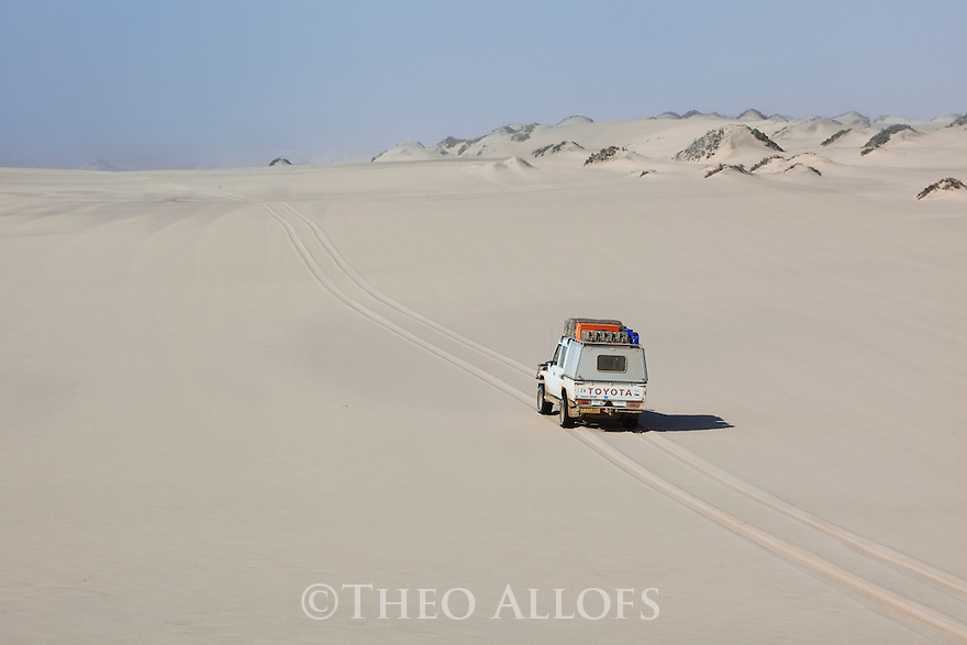 Namibia;  Namib Desert, Skeleton Coast, Northern Skeleton Coast National Park, 4x4 vehicle on dunes north of Moewe Bay