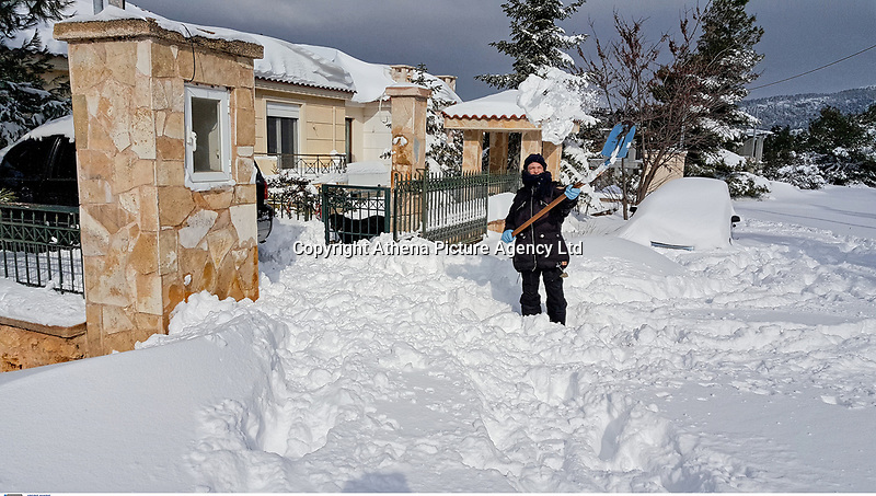 Pictured: A man ckears his driveway in the suburb of Afidnes near Athens, Greece. Tuesday 08 January 2018<br /> Re: Heavy snowfall has affected most parts of Greece.