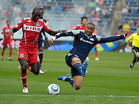 New England defender Darrius Barnes (25) tackles the ball away from Chicago forward Dominic Oduro (8).  The Chicago Fire defeated the New England Revolution 3-2 at Toyota Park in Bridgeview, IL on Sept. 25, 2011.