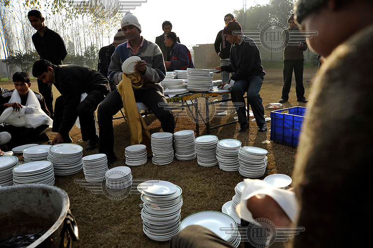Workers wash and sort dishes at Grewal Farms, one of many wedding reception centres in Amritsar which employs hundreds of staff during the wedding season to work around the clock hosting day and night marriage ceremonies and parties.