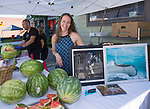 Photographer Sayde Lynn serves up watermelon and shows off her art at the Midtown Art Walk on Thursday afternoon in Reno, June 28, 2018.