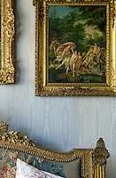 A gilt-framed painting of nymphs hangs against a silk-covered wall above the bed