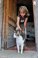 Girl (9) caressing cat at doorstep (Licence this image exclusively with Getty: http://www.gettyimages.com/detail/93522416 )