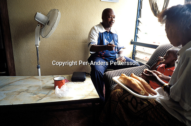 KINSHASA, CONGO - FEBRUARY 28: Kabanga Makolo Robert, age 48, and his wife Kiawanga Marie Robert, age 38, and their baby Apika eating breakfast in the living room of their flat on February 28, 2002 in Lingwala district in Kinshasa, Congo. Mr. Robert has lived in the 2 room flat for 20 years. He is a junior bank inspector at a local bank, and his wife is a housewife. They live a middle class life in Kinshasa, a few of the lucky ones to have a job that pays a little bit more than being an civil servant. Civil servants are paid about $ 10 a month in Congo. .(Photo: Per-Anders Pettersson/ Getty Images).