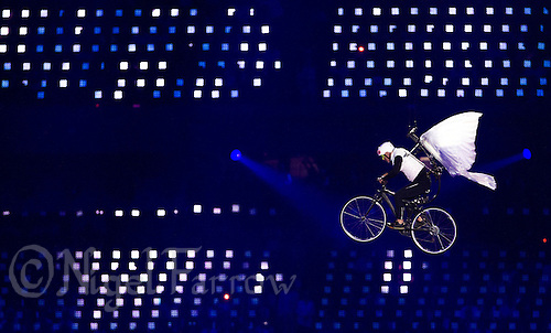 "27 JUL 2012 - LONDON, GBR - A performer dressed as a dove to represent a Dove of Peace attempts to cycle out of the Olympic Stadium during the ""Bike a.m."" section of the Opening Ceremony of the London 2012 Olympic Games in the Olympic Park, Stratford, London, Great Britain (PHOTO (C) 2012 NIGEL FARROW)"