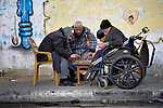 Old men play a game on a sidewalk in Gaza.