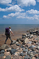 A backpacker hikes a cobblestone beach near Au Sable Point in Pictured Rocks National Lakeshore near Grand Marais, Mich.