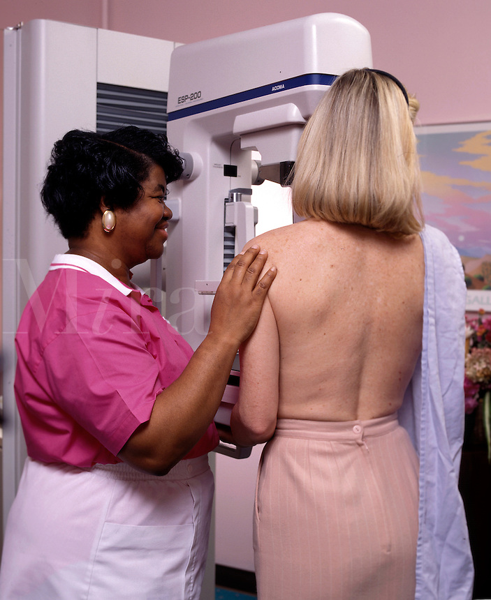 Tech assists patient undergo a mammography test.
