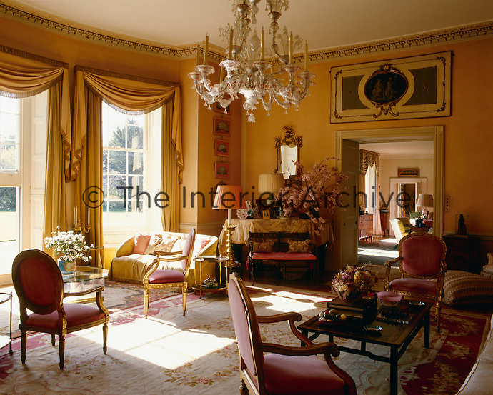 The drawing room at Hambledon is furnished in traditional style with sash windows opening onto the garden