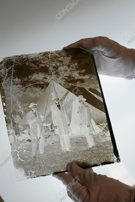 "An original 8x10"" glass plate negative, shot at the site of the Battle of Antietam, 1862, of President Lincoln (center), Mr. AllanPinkerton (L) and General McClerand. A Library of Congress archivist holds the negative over a light table. Washington D.C., June 3, 2005"