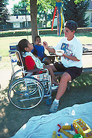 Foster mom feeding disabled kids in wheelchairs age 42 and 8.  Minneapolis Minnesota USA
