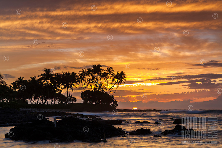 A fiery sunset silhouettes palm trees and a rocky shoreline at Pauoa Bay, Big Island.