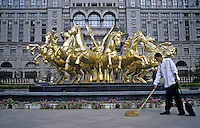 A cleaner sweeps in front of a gold foil sculpture of Apollo at a luxury apartment in CBD of Beijing, China..24 Jul 2005