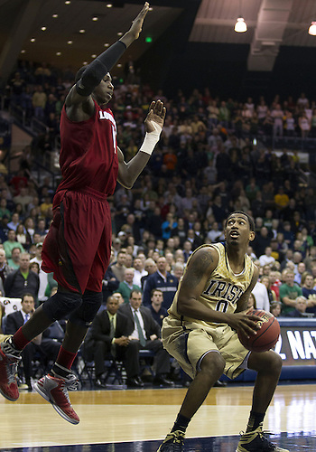 February 10, 2013:  Notre Dame guard Eric Atkins (0) looks to shoot the ball as Louisville center Gorgui Dieng (10) defends during NCAA Basketball game action between the Notre Dame Fighting Irish and the Louisville Cardinals at Purcell Pavilion at the Joyce Center in South Bend, Indiana.  Notre Dame defeated Louisville 104-101 in five overtimes.