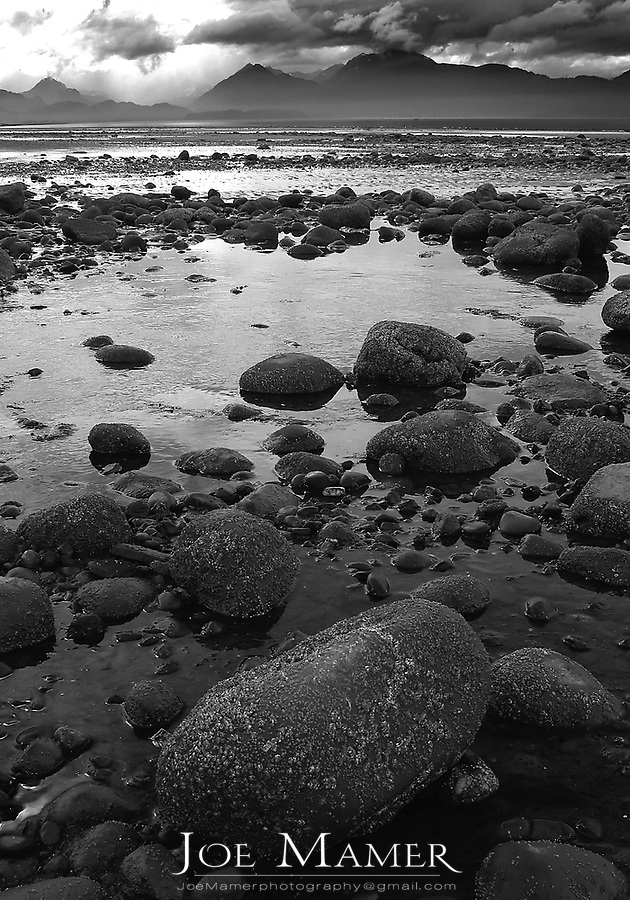 Rocks and dramatic clouds during low tide at Kachemac Bay, Homer, Alaska