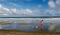 A boy pulls a toddler through a tide pool at low tide on a beach.