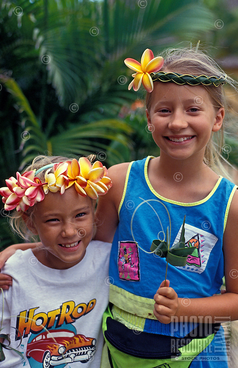 Girls with ti leaf craft items and plumeria.