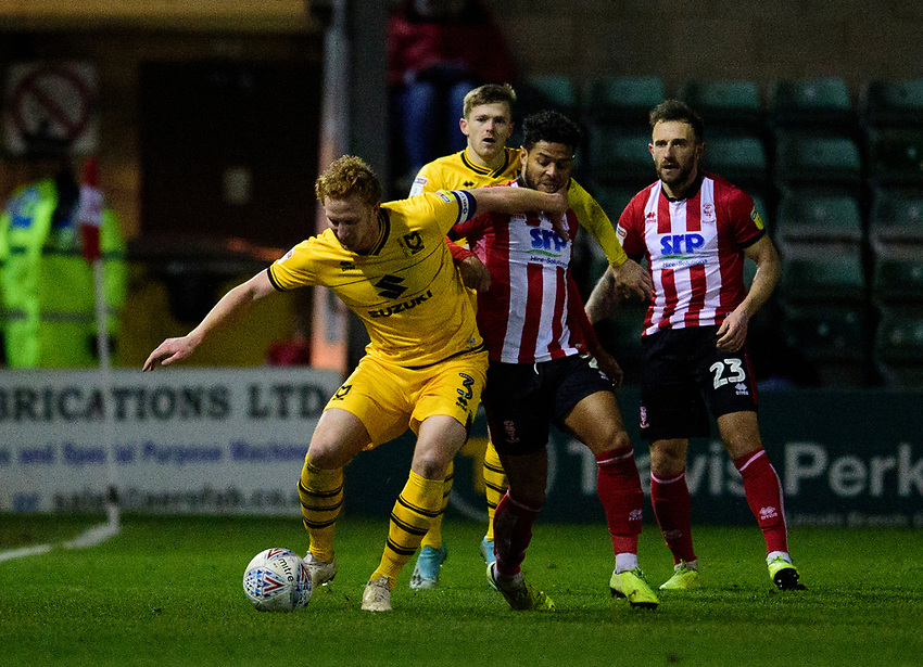 Milton Keynes Dons' Dean Lewington shields the ball from Lincoln City's Tyreece John-Jules<br /> <br /> Photographer Andrew Vaughan/CameraSport<br /> <br /> The EFL Sky Bet League One - Lincoln City v Milton Keynes Dons - Tuesday 11th February 2020 - LNER Stadium - Lincoln<br /> <br /> World Copyright © 2020 CameraSport. All rights reserved. 43 Linden Ave. Countesthorpe. Leicester. England. LE8 5PG - Tel: +44 (0) 116 277 4147 - admin@camerasport.com - www.camerasport.com