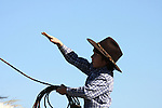 A young cowboy throwing the rope from horseback