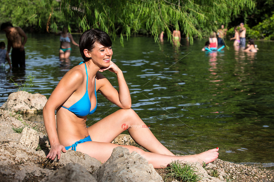 Smiling modern female sunbathing during summer at Barton Creek, a scenic Austin swimming hole and spring-fed creek feeding into Lady Bird Lake.