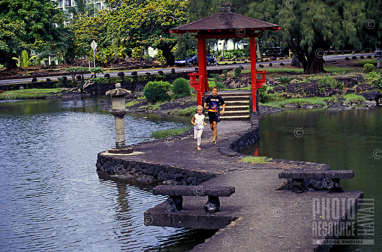 Two young children run down a bridge over a pond at Queen Liliuokalani Park in Hilo, which is modeled after an authentic Japanese garden.