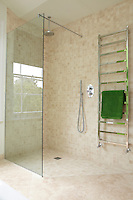 A shower area with a glass screen in a modern bathroom tiled in neutral tones. A green towel hangs on a stainless steel wall-mounted radiator.