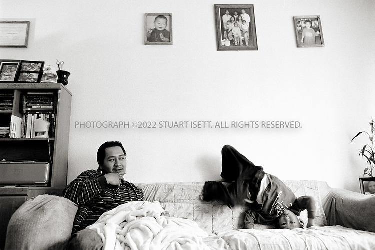 6/7/2007--Tacoma, WA, USA Yadang Moth, 34, at home with his son. Facing deportation, Yadang refuses to marry his girlfriend, affraid that he will simply have to divorce her once he is sent back to Cambodia. He works a series of jobs, paid under the table as he does not having working papers for the US. ©2007 Stuart Isett. All rights reserved.