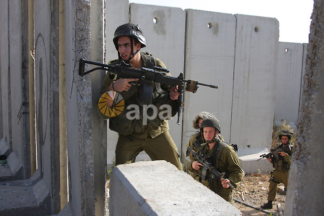 "An Israeli soldiers walk along the controversial Israeli barrier after a protest in the Qalandia refugee camp, near the West Bank city of Ramallah, on November 9, 2009 to mark the 20th anniversary of the fall of the Berlin Wall in Germany. Palestinians are using the anniversary of the end of the Berlin wall to press their campaign against Israel's ""wall"", mostly a razor-wire fence interspersed with concrete barricades which Israel began building around the West Bank in 2002. The Jewish state has come under international censure for the barrier's de facto annexation of occupied West Bank land.. Photo by Issam Rimawi"