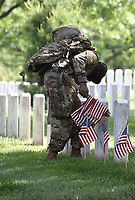 ARLINGTON, VA - MAY 21: US Soldiers place flags at Arlington Cemetery. Due to COVID extra soldiers have been added to insure that all headstones have a flag placed for Memorial Day on May 21, 2020 in Arlington, Virginia. <br /> CAP/MPI34<br /> ©MPI34/Capital Pictures