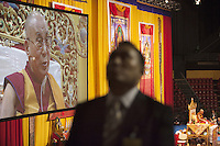 "Switzerland. Basel. St. Jakobshalle. His Holiness the Dalai Lama is on stage during his public lecture on Bodhicitta. The topic of his talk is about Nagarjuna's Commentary on Bodhicitta which touches on two aspects of the awakening mind, the twin qualities of wisdom and compassion, which are necessary for anyone who aspires to be a better person and implement changes in their lives. The 14th and current Dalai Lama is Tenzin Gyatso, recognized since 1950. He is the current Dalai Lama, as well as the longest-lived incumbent, well known for his lifelong advocacy for Tibetans inside and outside Tibet. Dalai Lamas are amongst the head monks of the Gelug school, the newest of the schools of Tibetan Buddhism. The Dalai Lama, also called "" Ocean of Wisdom"" is considered as the incarnation of Chenresi, the Bodhisattva of compassion who is also the protective deity of Tibet. The man in front is a tibetan man working as a body and security man for the Dalai Lama. 7.02.2015 © 2015 Didier Ruef"