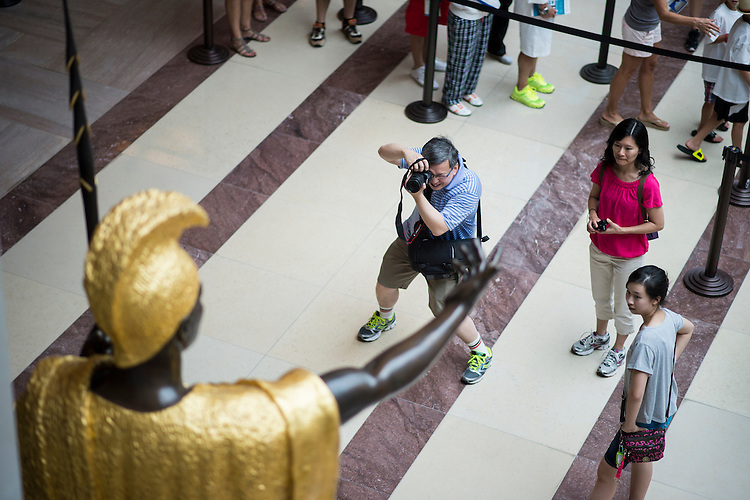 UNITED STATES - JULY 22: Tourists take photos in the Capitol Visitor Center at the base of the King Kamehameha I statue on Monday, July 22, 2013. (Photo By Bill Clark/CQ Roll Call)