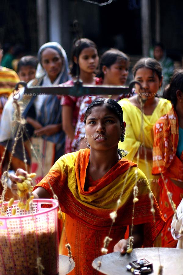 Bangladesh. Women wait in line while another one collects and weighs cocoons at a BRAC center...Bangladesh. Des femmes font la queue pendant qu'une autre collecte et pèse leur cocons dans un centre du BRAC.
