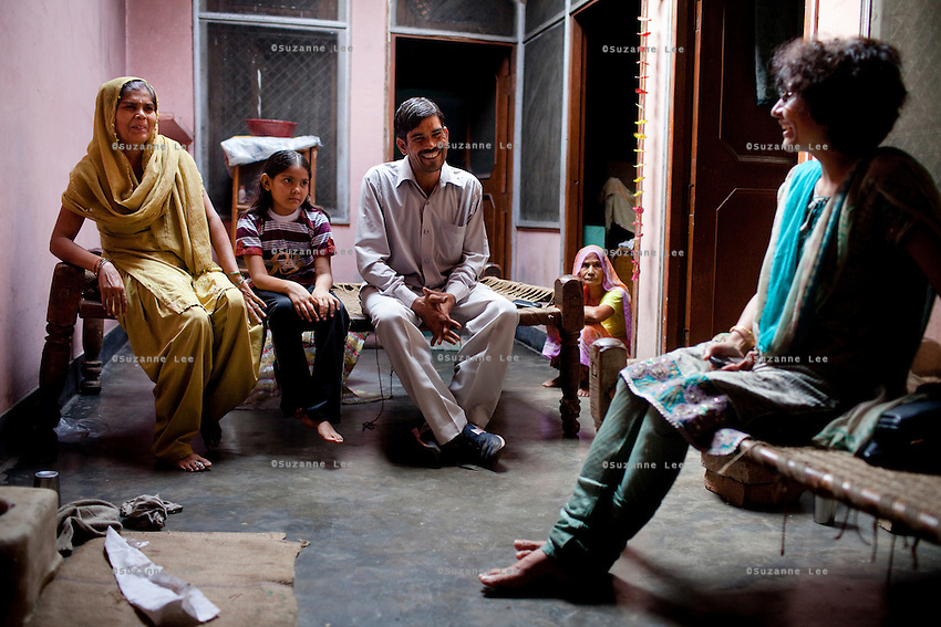Jagroshan Sharma (aged 36, centre) sits with his family as they speak with Dr. Meenal Mehta in their house in Ghaziabad, Uttar Pradesh, India. Jagroshan had chosen to do a non-scalpel vasectomy (NSV) for many reasons. He wanted to be an equal partner in the relationship, knew that NSV was less complicated and will not put his wife through numerous problems, and wants his two children to do well in life and study in  English medium schools despite his modest earnings. He now works part time as a link worker under the tutelage of Dr Meenal Mehta (extreme right) who works with USAID on the NSV project in Uttar Pradesh, India. She is well reputed to be responsible for the increased NSV acceptance in Ghaziabad and Bulandshar districts. Photo by Suzanne Lee / Panos London