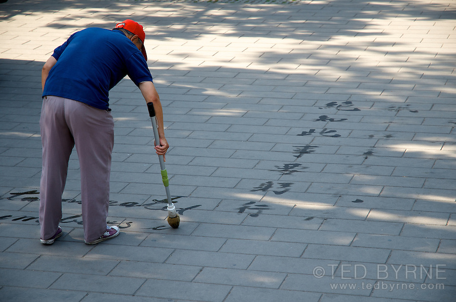 Chinese man water painting on patio with large brush (Beijing)