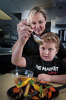 Chef Jennifer Russo shows her son Cooper, 8, how to finish off roasted tri-color carrots with herb butter nad Arizona honey, while working in her kitchen at The Market by Jennifer in Phoenix.