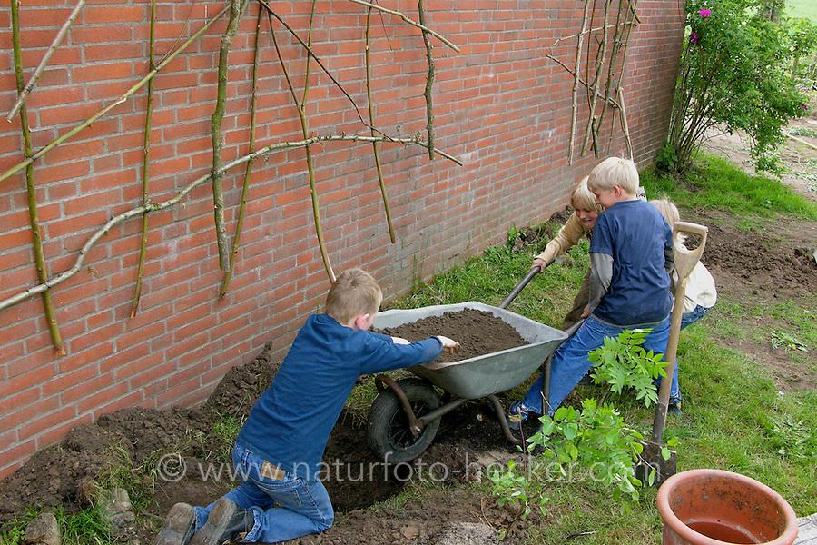 Fassadenbegrünung im Schulgarten, Begrünung einer Fassade, Garten der Grundschule Nusse wird als Projektarbeit von einer 1. Klasse gestaltet, Kinder bringen frischen Mutterboden zur Bodenverbesserung in die Beete der Rankpflanzen ein, Gartenarbeit