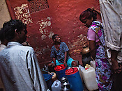 Local slum dwellers queue to collect water from a pipe in their slum in Govind Puri, New Delhi, India.