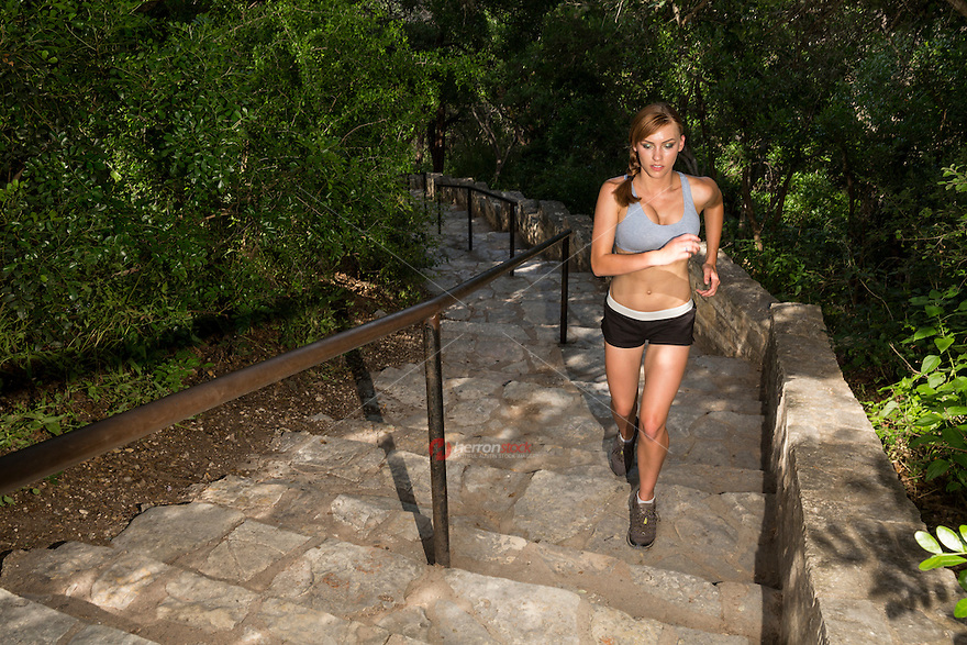 Woman runner training for marathon runs up hundreds of physically demanding stairs at Mount Bonnell Lookout Point over Lake Austin.