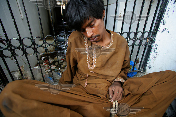 A drug user lies slumped in the Pakistan Society for Injecting Drug Users, a drop-in centre in the Gulshan-e-Iqbal area of Karachi. The centre runs HIV prevention and awareness projects as well as supplying drug users with clean needles.