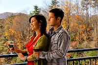 A man and woman, holding a glass of wine, looks out over the Blue Ridge Mountains from a balcony in Asheville NC's Biltmore Park Town Square, a planned community of residential living, office spaces and shopping.