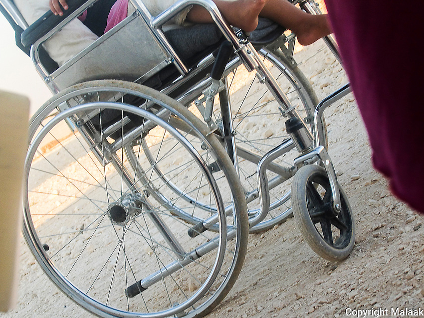 The wheelchair is for old people. She is one year and one month old. In front of her is her mother who has taken care of her for many months.