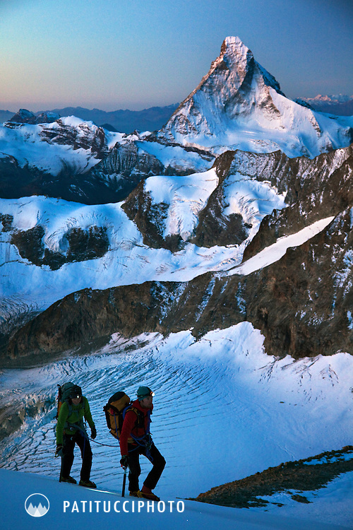 Two alpine climbers using headlamps as they climb in the Swiss Alps in the pre-dawn hours. The Matterhorn is behind them, high above Zermatt, Switzerland