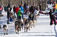 Robert Bundtzen and team run past spectators on the bike/ski trail during the Anchorage ceremonial start during the 2014 Iditarod race.<br /> Photo by Britt Coon/IditarodPhotos.com