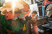 A young dhobi brushes his teeth while a worker carries a load of clothes to the Laundromat in Dhobighat in India's financial capital, Mumbai, India. The laundry comes from different sections of the society - from hospital to hospitality to garment factories and normal households.