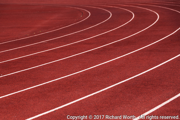 Lines and shapes they make create an abstract reminiscent of a planet's rings on a high school track.