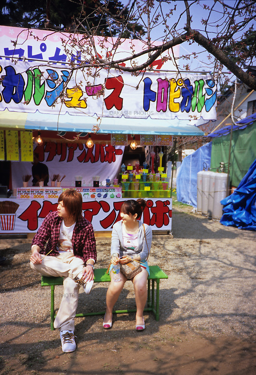 A Japanese couple rest on a bench in front of a food stool of tropical juice during the cherry blossom festical at Hirosaki Castle, Aomori.